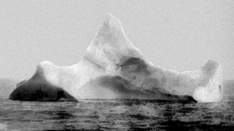 This is believed to be the iceberg that Sank the Titanic. Photo taken after the collision, showing signs of collision and red paint. Courtesy US Coast Guard